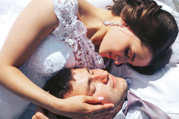 The bride and groom lie on a green meadow and bask in the sun