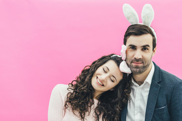 Young tender pair standing on a pink background. Bunny on his head. The wife gently put her head on her shoulder with her eyes closed. The concept of Easter.
