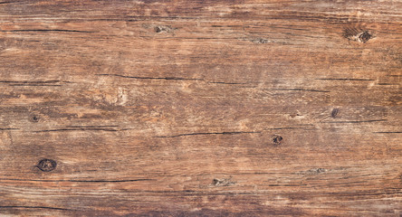 Wood texture background. Top view of vintage wooden table with a cracks. Brown rustic rough wood for backdrop. Surface of old knotted wood with nature color, texture and pattern.