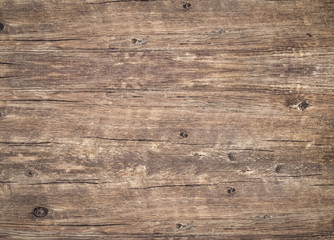 Wood texture background. Top view of weathered vintage wooden table with cracks. Brown rustic rough wood for backdrop. Surface of old knotted wood with nature color, texture and pattern.