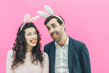 Young happy couple standing on pink background. On the head of the ears of the bunny. During this man and his wife hold small carrots in their lips. Look at each other. Easter.