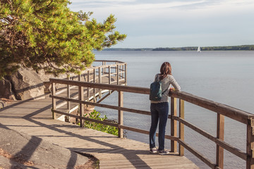 Wooden Pathway or Footpath near lake. Path along the water. Beautiful landscape with way between stones and lake. Swedish nature. Woman looks into the distance. Wall mural