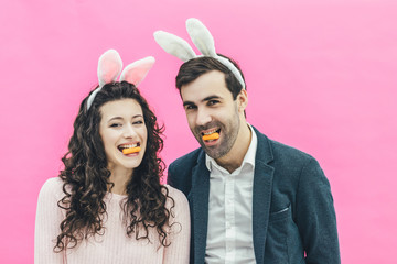 Young happy couple standing on pink background. On the head of the ears of the bunny. During this man and his wife hold small carrots in their lips. Sincerely looking at the camera.