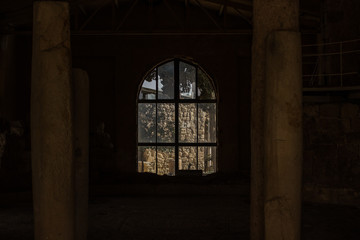 ruined abandoned stone house building inside with symmetry columns and arch window frame in twilight darkness