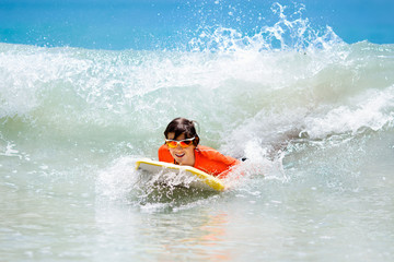 Child surfing on tropical beach. Surfer in ocean.