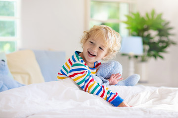 Child playing in bed. Kids room. Baby boy at home.