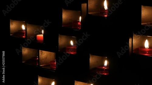 Beautiful red church candles for prayers in special niches in a