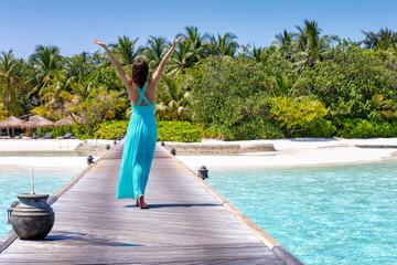 Glückliche Frau in blauem Sommerkleid läuft auf eine tropische Insel auf den Malediven zu und genießt ihren Urlaub