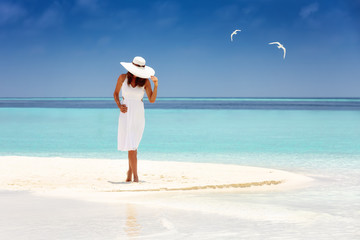 Attractive traveler woman in a white dress and sunhat stands on a tropical beach with turquoise waters and white sand