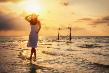Elegant woman standing on a tropical beach and enjoying the sunset during her vacation time