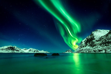 Beautiful green Northern Lights at Haukland Beach on the Lofoten Islands in Norway