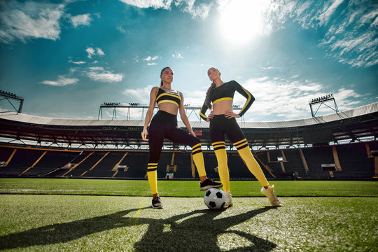 Two athletic sporty women from one team in sportswear with soccer ball on stadium.