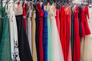Beautiful elegant evening dresses on hangers in the showroom.