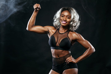 Sporty beautiful afro-american bodybuilder model, woman in sportwear makes fitness exercising at black background to stay fit