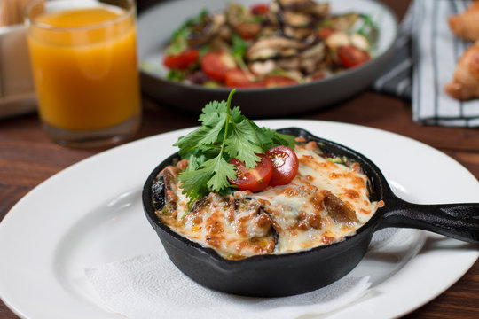 Grilled eggplant stuffed with tomatoes, nuts, pomegranate and herbs and cheese, baked in a black pan. Wood background