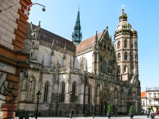 Kosice, Slovakia - May 2, 2018: Beautiful Gothic Cathedral of St. Elizabeth in Kosice. Ancient stone temple with a brown roof, a clock tower and stucco on the walls on a sunny spring-summer day