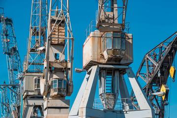 Alter, rostige Hafenkräne mit blauem Himmel