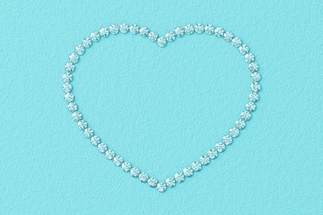 Heart-shaped frame made of small diamonds on turquoise textured background