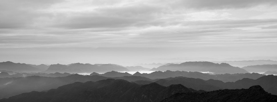 Abstract Image, Mountain Silhouettes at dawn - rolling jagged mountain peaks, monochrome hues. Panoramic Abstract Background Image, overcast skies, layers of rolling mountains in the distance.