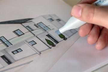 Architekt coloriert einen Hausentwurf mit Marker