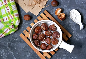 Fried edible chestnuts in a white ceramic pan on a dark gray concrete background. Top view.