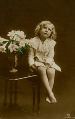 Young Girl Sitting on Table with Vase of Flowers