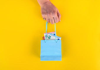 female hand hold little shopping bag with euros money