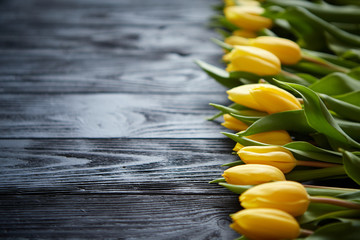 Composition of fresh yellow tulips placed in row on black rustic wooden table