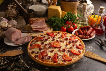 Pizza with ham and smoked sausages for a restaurant menu.