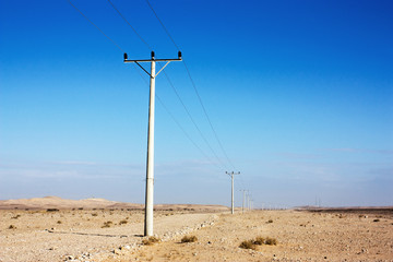 Electric power poles in desert of Jordan. High voltage powerlines. Early morning in wilderness after sunrise.