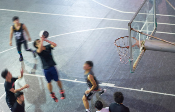 High angle view of young Asian people playing basketball outdoor at night