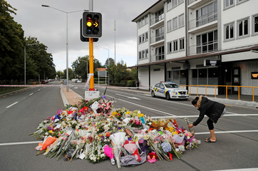 A woman places flowers at a memorial as a tribute to victims of the mosque attacks, near a police line outside Masjid Al Noor in Christchurch
