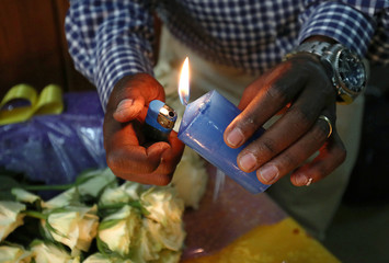 A Kenyan man lights a candle at a prayer session, as they mourn their relatives, during a commemoration ceremony for the victims at the scene of the Ethiopian Airlines Flight ET 302 plane crash, at the Kenyan Embassy in Addis Ababa