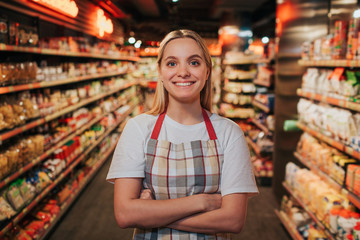 Busy young woman stand in line between shelfs with pasta. She pose on camera and smile. Happy positive model.