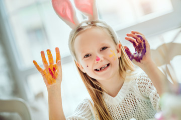 Preparing for the celebration of Easter. A little girl wearing a bunny ear shows painted hands.