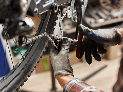 Cropped shot of male mechanic making service in bicycle repair shop, repairman fixing mountain bike chain using special equipment, wearing protective gloves