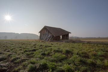 Abbruchreife verrottete Holzhütte auf einer grünen Wiese in Bayern