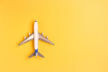 Flat lay airplane on yellow background. Concept of travel.