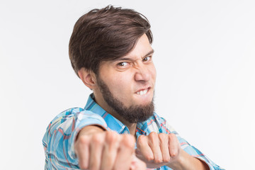 Expression and gesture concept - Portrait of angry man showing his fists on white background