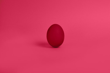 One red painted Easter egg stand on a pink background. Happy Easter holiday card or banner.
