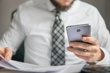 Office work with a laptop. Light background. Holding smartphone in hand. Businessman work with computer on table in office work. Young bearded businessman. Financial business.