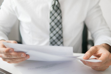 Light background. Financial business. Businessman work with computer on table in office work. Holding smartphone in hand. Young bearded businessman. Office work with a laptop.
