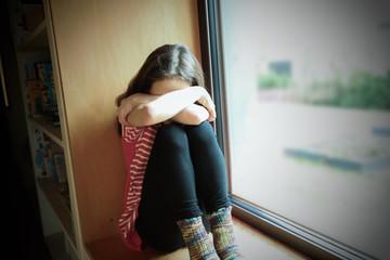 Ein Mädchen sitzt ängstlich auf der Fensterbank