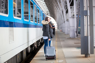 Pretty young woman with luggage waiting at the traint station for her train, transportation concept
