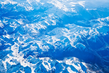 Airplane view of blue mountains covered with white snow. Can be used as nature background