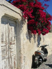 Scooter Vintage doorway in Santorini with red flowers and scooter motorcycle