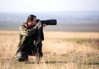 Wildlife, nature man photographer in camouflage outfit shooting, taking pictures