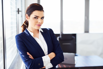 Confident businesswoman looking at camera in modern office.