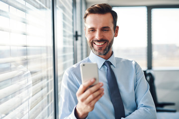Happy businessman checking his phone standing in modern office