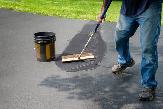 Homeowner spreads blacktop asphalt sealant on driveway